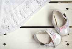 Flat lay of lovely white vintage patent leather baby shoes with pink bows and laces standing and white hand made knitted cardigan Stock Photography