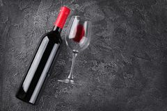 Flat lay with lying red wine bottle and glass for tasting. On gray concrete background royalty free stock images