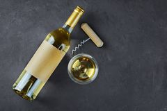 Flat lay of lying white wine bottle with empty label, corkscrew and glass for tasting. On dark gray concrete background stock images