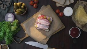 Flat lay of making the sandwich with sliced bacon, pickle and vegetables on the wooden board in the beam of light. Making of the fastfood at home, meat cooking stock video