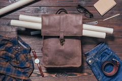 Flat lay with male shirt, jeans, watch and blueprints in backpack arranged. On wooden tabletop Stock Images