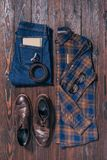 Flat lay with male stylish shirt, shoes, jeans, eyeglasses and belt arranged. On wooden surface Stock Photography