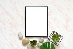 Flat lay marble desk with white empty frame for text, stones and succulents background Royalty Free Stock Images