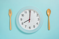 Flat lay of meal time, wall clock spoon and fork on pastel blue stock images