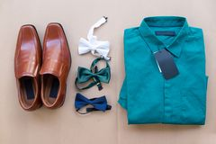 Flat lay of men casual fashion outfits. On brown background brown shoes, green shirt and various bow tie Stock Image