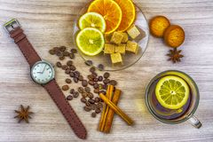 Flat lay. Men`s watches with leather strap. Slices of lemon and orange on a saucer. Cup of tea with lemon. Coffee beans, cookies stock photos