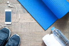 Flat lay of mobile phone with earphone and sport equipment. On wood background. Sport accessories, Sport equipment, top view Stock Photos