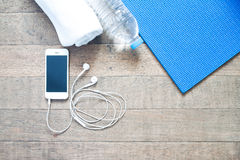 Flat lay of mobile phone with earphone and yoga mat Stock Photography