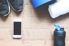 Flat lay of mobile phone with sport equipments on wood background. Stock Photos
