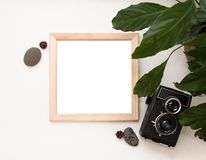 Flat lay mock up, top view, wooden frame, old camera, plant and stones. Interior layout, square poster mockup, wood frame. stock photos