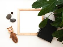 Flat lay mock up, top view, wooden frame, toy squirrel, plant, note pad. Interior layout, square poster mockup, wood frame. royalty free stock photography