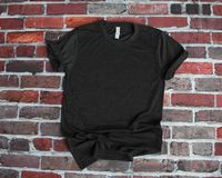Flat lay mockup of charcoal gray tshirt on brick background royalty free stock image