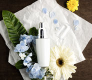 Flat lay moisturizer cream with flowers on craft paper and dark Stock Images