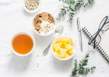 Flat lay morning breakfast inspiration - greek yogurt with whole grain cereals, tea, pineapple and notepad, glasses on a light bac stock photography