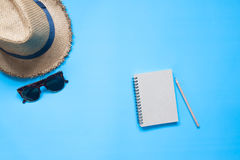 Flat lay of notebook with pencil, hat and sunglasses on blue Royalty Free Stock Images