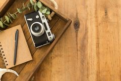 Flat lay with notepad, black pen and vintage camera. Flat lay with notepad, black pen and vintage film camera in wooden tray over rustic wooden tabletop. Copy Royalty Free Stock Photos