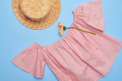 Flat lay of an off-the-shoulder swing blouse with straw hat Royalty Free Stock Image