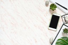 Flat lay office marble desk with phone, frame and notebook copy space background Stock Photos