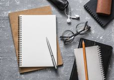 Flat lay office workplace. Business or education accessories - blank notepad glasses, pens, pencils, headphones on grey background. Top view. Space for text Royalty Free Stock Photography