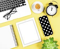 Flat lay office workplace Laptop notebook tablet coffee yellow b. Flat lay office workplace. Laptop, notebook, tablet PC, coffee, succulent plant, alarm clock on Royalty Free Stock Photos