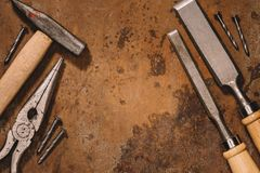 Flat lay with old shabby mechanical tools. On brown surface royalty free stock photo