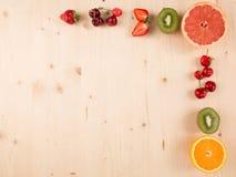 Flat lay of orange,kiwi, cherry, strawberry on wooden background Stock Photos
