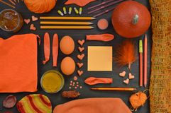 Flat lay with orange objects mixed together on brown. Flat lay with orange objects like pumpkin, pencils, wool, feather, clay hearts, leaf, curry powder, jam stock photography