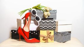 Top view outfit composition trendy female accessories red shoes sunglasses handbag clutch and tulips flowers on carton boxes on royalty free stock photography