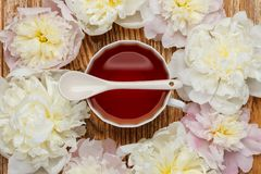Flat lay over wooden background with peonies, cup of tea and spo Stock Image