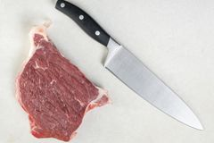 Flat lay overhead view above raw beef steak witk kitchen chef knife on the white marble background table.  Stock Photos