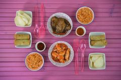 Flat lay table setting with Chinese food dishes and forks ready to eat. A flat lay overhead view of a bright pink wood table with dishes of Chinese or oriental Stock Images