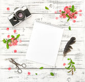 Flat lay paper sketchbook photo camera pink spring flowers. Flat lay with paper sketchbook, photo camera, pink spring flowers on white wooden background stock image