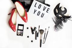 Fashion flat. Flat lay of party preparation accessories. top veiw: red high heels shoes, cosmetics and brushes, black mask and I love you note on a word table Royalty Free Stock Photo