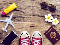 Flat lay of passport , mobile , plane model , red sneakers. And traveler`s accessories items on wooden background with copy space. travel and vacation concept royalty free stock images