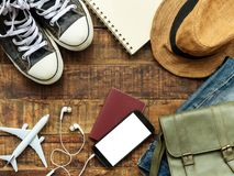 Flat lay of passport , mobile , plane model , sneakers and travel. Er`s accessories items on wooden background with copy space. travel and vacation concept stock images