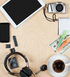 Flat lay of personal stuff, tablet computer,cards, coffee, money, camera photo and other. Flat design and top view on desk as fram. E with blank center on wood royalty free stock image
