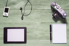 Flat lay of personal stuff, tablet pc, camera photo,notebook and other. Flat design and top view on green wooden background. Mockup consisting of tablet pc in royalty free stock photo
