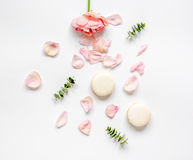 Flat lay with petals and macaroons on white background top view Stock Photos