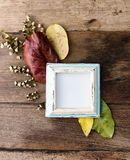 Flat lay photo frame with autumn leaves on old table. Rustic mock up, background Stock Images