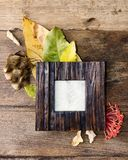 Flat lay photo frame with autumn leaves on old table Stock Photography