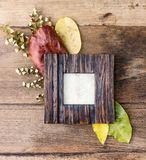 Flat lay photo frame with autumn leaves on old table. Rustic mock up. Background Stock Photos
