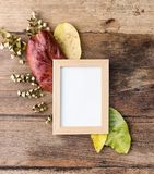 Flat lay photo frame with autumn leaves on old table. Rustic mock up