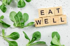 Flat lay photo - leaves of cornsalad Valerianella locusta with text EAT WELL at wooden blocks on white working board. Green. Leaves healthy eating concept royalty free stock photo