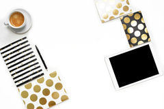 Flat lay photo of minimalistic white office desk with tablet, cup coffee and stylish gold notebook copy space background stock image
