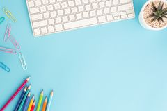 Flat lay photo of office desk with pencil and keyboard ,top view workpace on blue background and copy space stock photos