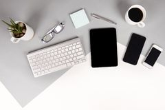 Flat lay photo of Office table with keyboard, notebook, digital tablet, mobile phone, Pencil, eyeglasses on modern two tone. White and grey background. Desktop royalty free stock photos
