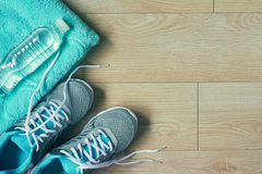 Flat lay photo of sports equipment. Sneakers,towel,bottle of water, top view, toned image over wooden background with copy space Stock Photography