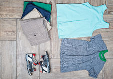 Flat lay photography of some boy's casual outfits. Boy's casual outfits on wood board background royalty free stock photography