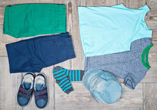Flat lay photography of some boy's casual outfits. Boy's casual outfits on wood board background royalty free stock photos