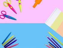 Flat lay picture of colored pencils, notepad and scissors lined on a smooth surface isolated background of halved in blue and pink royalty free stock photos